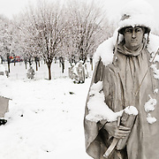 "The Korean War Memorial on the National Mall on a snowy winter morning after fresh snow. The Korean War Veterans Memorial, unveiled in 1992, sits on the northwestern end of the National Mall, not far from the Lincoln Memorial. It consists of several elements designed by different people and groups. It has a triangular footprint with the main elements being ""The Column"" consisting of 19 stainless steel solders, each over 7 feet tall, and a reflective granite wall etched with the faces of thousands of Americans who lost their lives in the war. At one end of the triangle, behind the soldiers, is a grove of trees. At the other is a large American flag and a small Pool of Remembrance. Among the designers were Frank Gaylord (the soldiers) and Louis Nelson (the reflecting granite wall)."