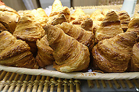 Freshly baked golden brown croissants resting on a pan in a French bakery or boulangerie.