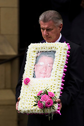© Licensed to London News Pictures . 30/08/2012 . Manchester, UK . A funeral director carrying a portrait of winnie Johnson outside St Chrysostom's Church, Victoria Park in Manchester on August 30, 2012, following Winnie Johnson's funeral. Winnie Johnson devoted her life to finding the body of her 12 year old son Keith Bennett who was murdered by Moors Murderer Ian Brady and Myra Hindley. Photo credit : Joel Goodman/LNP