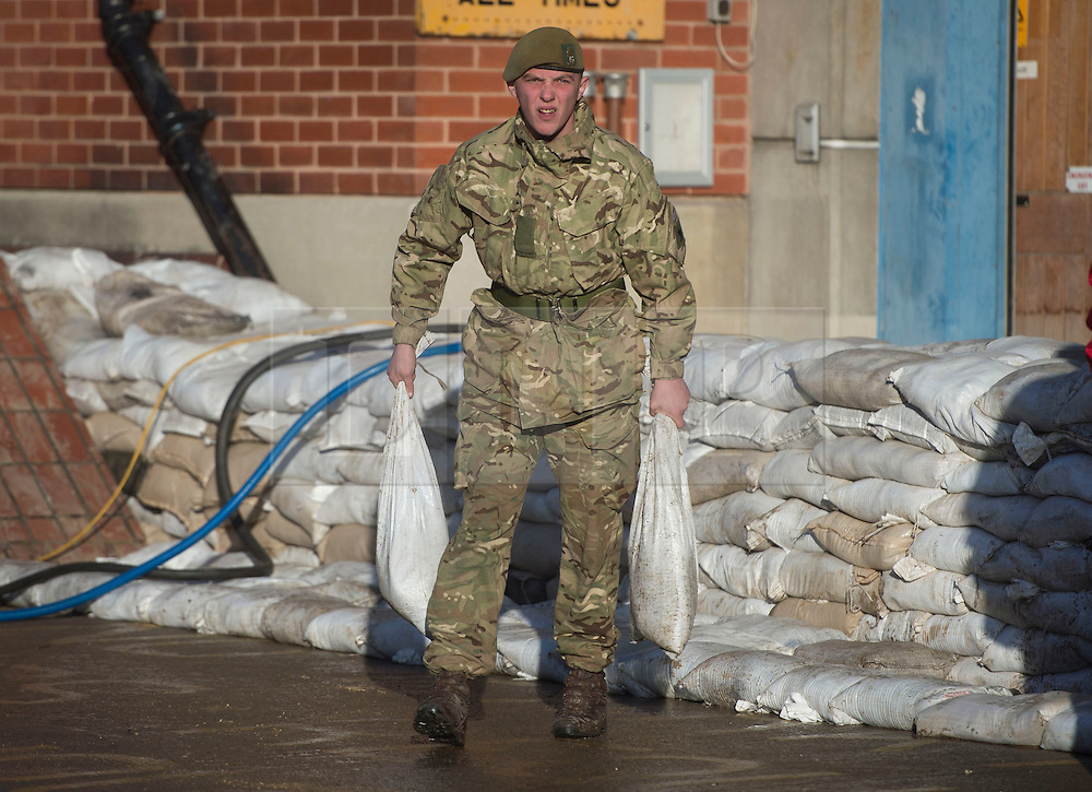 © Licensed to London News Pictures. 29/12/2015. York, UK. A soldier from 2nd Battalion The Yorkshire Regiment helps sandbag a British Telecom building to protect it from further flooding in the centre of York on December 29, 2015. Further rainfall is expected over coming days as Storm Frank approaches the east coast of the country. Photo credit: Ben Cawthra/LNP
