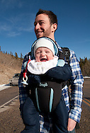 A father takes his smiling and very happ baby son on a walk in rural calgary in cold and winter conditions both wrapped up nice and warm.