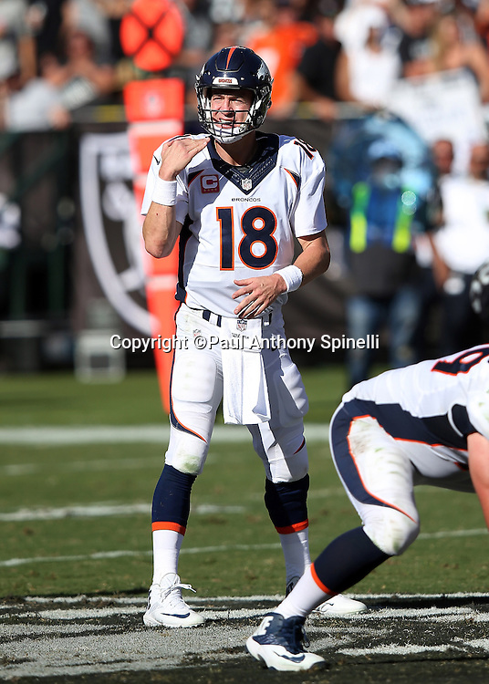 Denver Broncos quarterback Peyton Manning (18) gives a throat cutting gesture as he calls an audible in the shotgun formation during the 2015 NFL week 5 regular season football game against the Oakland Raiders on Sunday, Oct. 11, 2015 in Oakland, Calif. The Broncos won the game 16-10. (©Paul Anthony Spinelli)