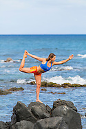 Olympic skier Julia Mancuso practicing yoga on the rocks in the ocean near her home on the island of Maui, Hawaii