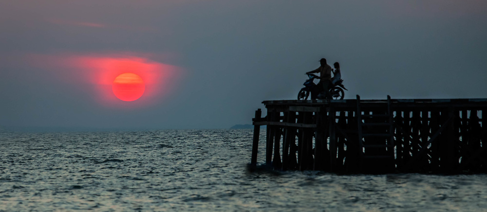 Motorcycle on Pier watching sunset over the ocean, Derawan Indonesia Borneo
