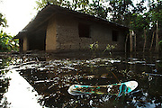 A sandal floats in floodwater next to a house that was badly damaged by floods in the village of Kotacomey, Benin on Monday October 25, 2010.