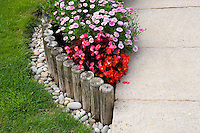 Wooden posts edging a flower bed with begonia