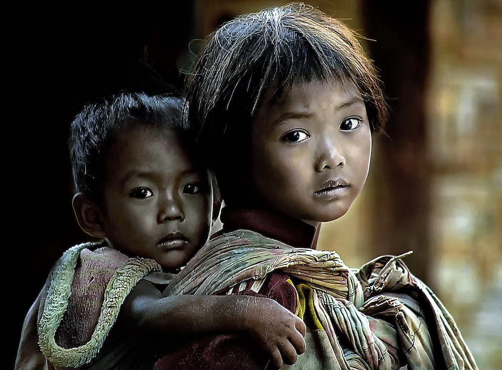 A girl cares for her brother near Luang Prabang, Laos.