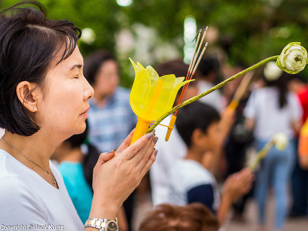 """13 MAY 2013 - BANGKOK, THAILAND:  A woman prays on Vesak in front of Wat That Thong in Bangkok. Vesak, called Wisakha Bucha in Thailand, is one of the most important Buddhist holy days celebrated in Thailand. Sometimes called """"Buddha's Birthday"""", it actually marks the birth, enlightenment (nirvana), and death (Parinirvana) of Gautama Buddha in the Theravada or southern tradition. It is also celebrated in Cambodia, Laos, Myanmar, Sri Lanka and other countries where Theravada Buddhism is the dominant form of Buddhism.    PHOTO BY JACK KURTZ"""