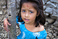 A young girl amidst the ruins of her family's house in Sipadol, Nepal, after the earthquake in April 2015.