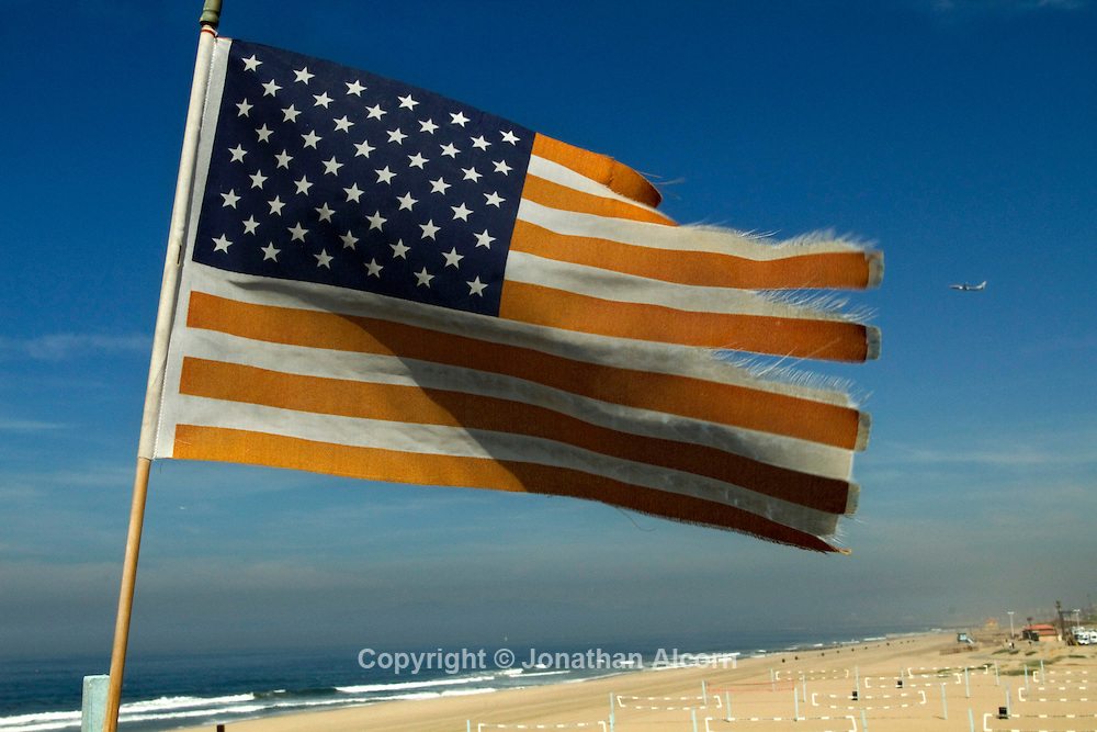 A miniature version of the flag of the United States of America flies in the wind on a bluff at Dockweiler Beach in El Segundo, CA.