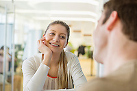 Smiling young woman looking at man in restaurant