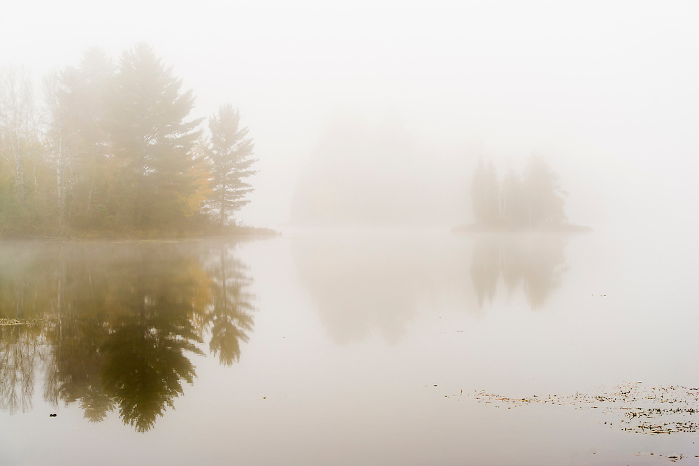 Fall color and fog shrouds a wilderness lake in the Hiawatha National Forest of Michigan's Upper Peninsula.