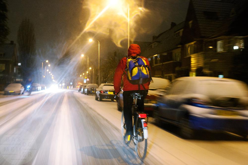 Een fietser rijdt op de Everard Meijsterlaan in Utrecht door de sneeuw.<br /> <br /> Cyclist in the snow