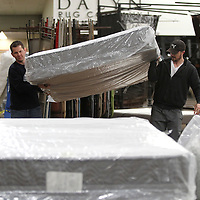 Adam Robison | BUY AT PHOTOS.DJOURNAL.COM<br /> Jacob Swims, VP of Sales for Southerland Bedding, and Matt Wolf, Director of Training, move mattresses as they prepare their show space for next weeks Tupelo Furniture Market Friday morning in Tupelo.
