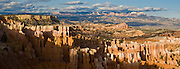 Sunset light strikes orange and white hoodoos in Bryce National Park, Utah, USA. Bryce is actually not a canyon but a giant natural amphitheater created by erosion along the eastern side of the Paunsaugunt Plateau. The ancient river and lake bed sedimentary rocks erode into hoodoos by the force of wind, water, and ice. (Panorama stitched from 3 photos.)
