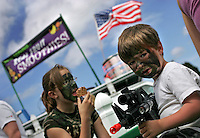 Gabriel McGhee, 4, right, came to Armed Forces Day with his toy M4.  At the annual Fort Lews event he and his aunt, Clare McGhee, background, eating ice cream, had their faces painted with camo, Saturday May 20, 2006. (Janet Jensen/The News Tribune)  ((NOTE TO COPY DESK I DON'T HAVE CLARE'S AGE))