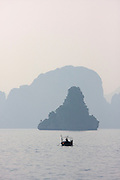 Halong Bay. Fishermen on rowing boats.