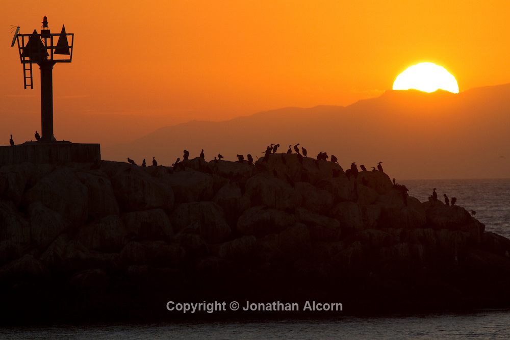 The Sun sets over the Santa Monica Mountains looking over the outer breakwater wall of Marina del Rey