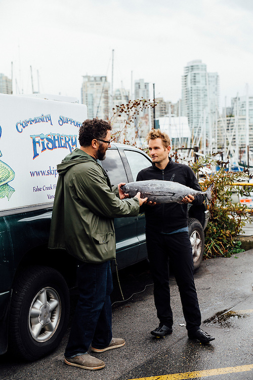 Chef Ned Bell with Shaun Strobel (green jacket) who runs Skipper Otto's a Community Supported Fishery (CSF). Fishermans Wharf, Vancouver, Canada.