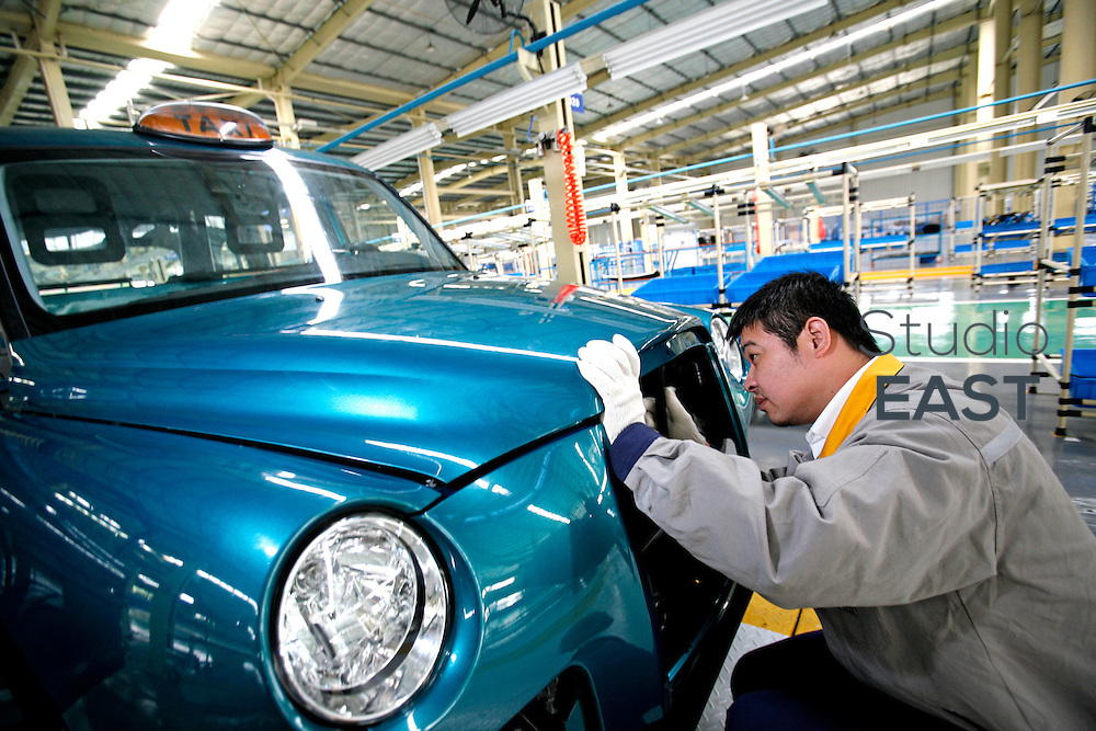 A worker works on an hand-built and hand-welded Taxi cab in SMA factory plant, in Fengjing, outside Shanghai, China, on October 24, 2008.  London Taxi International, the producer of London Taxi's famed black cabs, turned to China to drive overseas expansion. More than 8,000 London Taxis will be produced from the Chinese factory, more than double the annual output of the firm's historical factory plant in Conventry, England. Most of these cars will go to places like Singapore, Dubai, Moscow, that covet the image associated with the London Taxis' tradition of good service and durability. London Taxi International will continue to build 90 percent of the Taxi cabs used in Britain at Coventry. Photo by Lucas Schifres/Pictobank