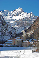 Ticino, Southern Switzerland. Valle Verzasca, Sonogno.  Pretty italianate church in the foreground with the magnificent snowy alps towering above.