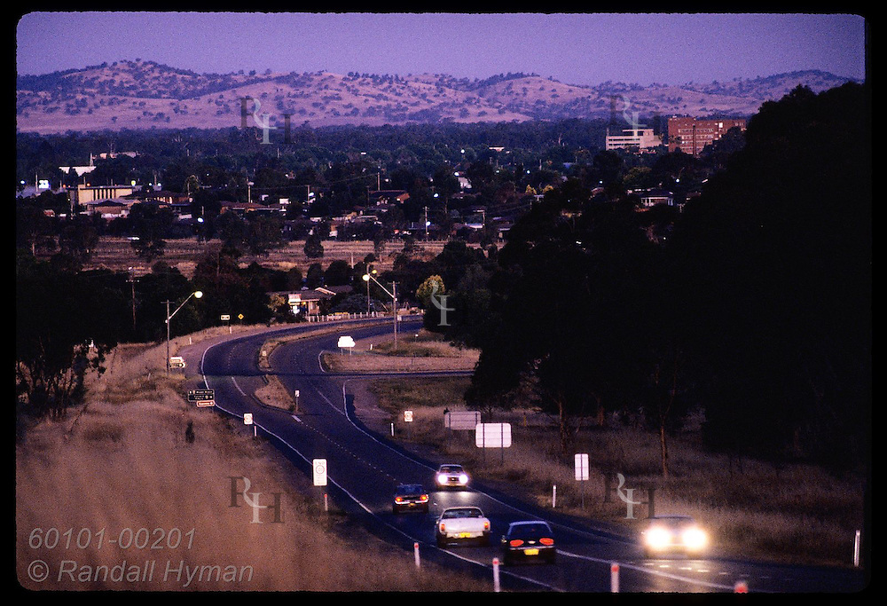Car lights cut through the dusk on highway into agricultural town of Wagga Wagga, New South Wales. Australia
