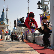 Visitors to Lotte World pose for photographs at the outdoor attractions. Lotte World is the world's largest indoor theme park which includes shopping malls, a luxury hotel, and an Ice rink. Opened on July 12, 1989, Lotte World receives over 8 million visitors each year. Seoul, South Korea. 21st March 2012. Photo Tim Clayton