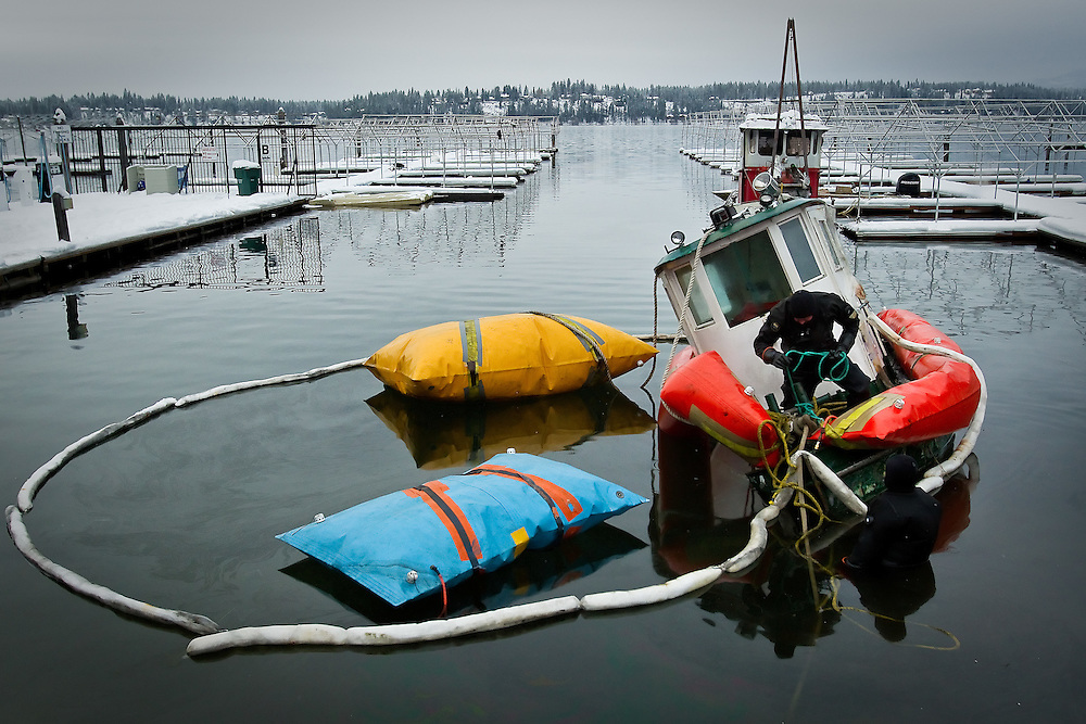 A diver unties lines used to pull a sunken tug boat to shore Monday that sank on Thanksgiving at the Hayden Lake marina. Crews used inflatable bags secured to the vessel to raise it off the lake bed and another tug and crane pulled it to shore.