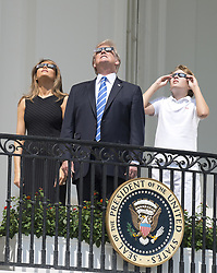 August 21, 2017 - Washington, District of Columbia, U.S. - United States President DONALD J. TRUMP, center, accompanied by first lady MELANIA TRUMP, left, and BARRON TRUMP, right, look at the partial eclipse of the sun from the Blue Room Balcony of the White House. (Credit Image: © Ron Sachs/CNP via ZUMA Wire)