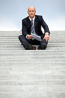 Portrait of businessman holding document on steps