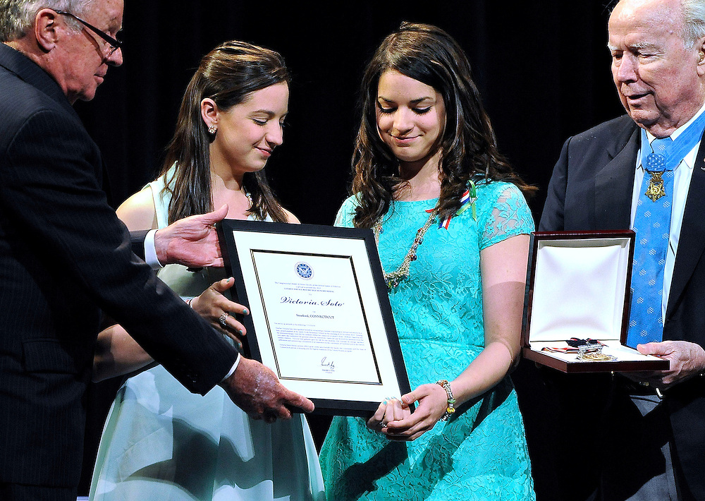 Sisters Jillian Soto, center left, and Carlee Soto, center right, accept the citizen honor of the Congressional Medal of Honor from Medal of Honor Recipient presenters, Thomas Kelley, left, and Bruce Crandall, right, on behalf of their late sister Victoria Soto in Newtown, Conn., Monday, May 6, 2013. The Congressional Medal of Honor Society says Rachel D'Avino, Dawn Hochsprung, Anne Marie Murphy, Lauren Rousseau, Mary Sherlach and Victoria Soto exemplified courage, sacrifice and selflessness in trying to protect students from the gunman at Sandy Hook Elementary School. (AP Photo/Jessica Hill)