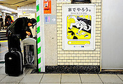 """A man digs around for discarded magazines to resell next to a poster requesting commuters refrain from lewd behavior on trains at an underground station in Tokyo, Japan. The Japanese are well known for their civility and politeness,  but a recent governmental campaign to clamp down on lewd behaviour that may inconvenienc others -- including talking on cell phones and applying makeup while commuting on a train -- was fueled by a decline in everyday etiquette and manners. The poster's headline reads """"Please do it at home."""""""