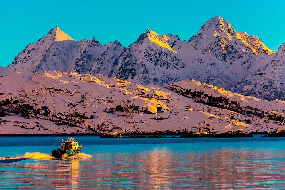 A boat departs the harbor in Svolvaer, on Austvagoya Island, Lofoten Islands, Arctic, Northern Norway.