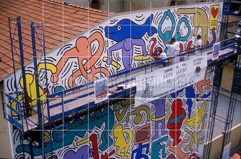"""Artist Keith Haring working at the mural """"Tuttomondo"""" on the rear wall of the Church of Sant'Antonio in Pisa, 1989 / L'artista Keith Haring mentre lavora al murale """"Tuttomondo"""" sul muro posteriore della chiesa di Sant'Antonio abate a Pisa, 1989 - © Marcello Mencarini"""