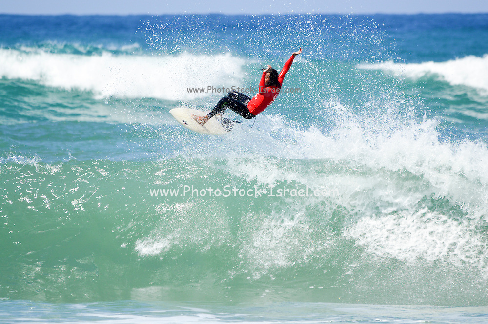 Surfer Jumps of the crest of a wave. Photographed in the Mediterranean Sea, Israel
