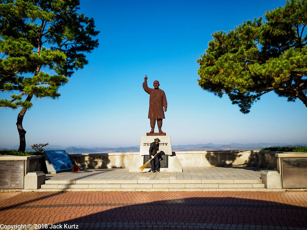 PAJU, GYEONGGI, SOUTH KOREA: A worker cleans up around the statue of Cho Man Sik, a Korean who fought against the Japanese colonization of Korea, at the entrance to Odusan Unification Observatory, a tourist attraction that overlooks the DMZ. Tourism to the Korean DeMilitarized Zone (DMZ) has increased as the pace of talks between South Korea, North Korea and the United States has increased. Some tours are sold out days in advance.      PHOTO BY JACK KURTZ