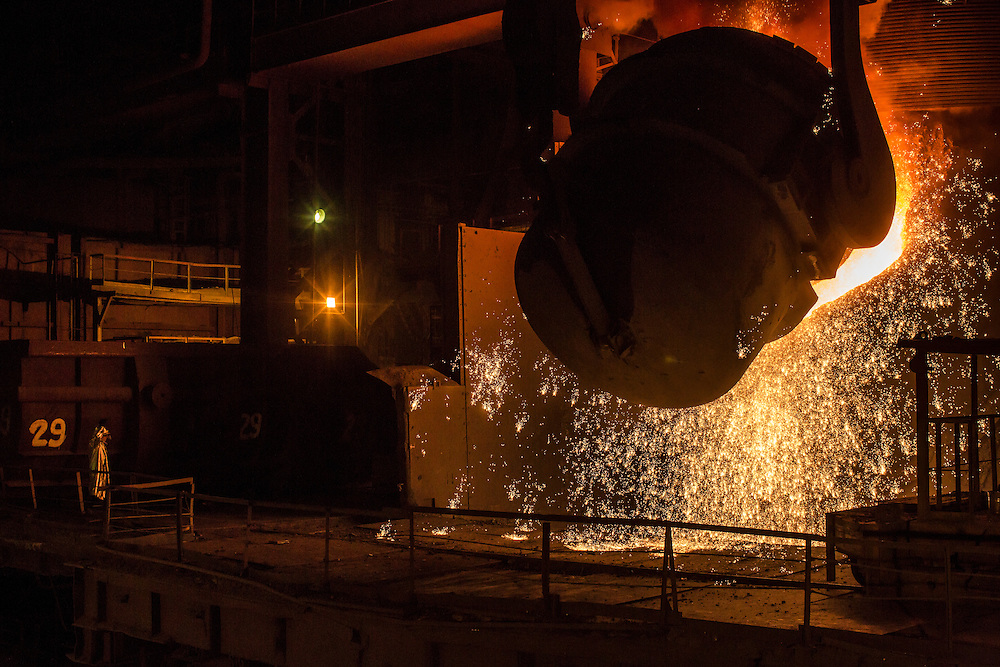 A worker tends the converter as molten iron is poured in at the Azovstal Iron and Steel Works on Friday, March 18, 2016 in Mariupol, Ukraine.