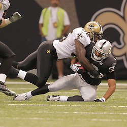 2008 October, 12: New Orleans Saints linebacker Jo-Lonn Dunbar (56) tackles on Oakland Raiders returner Tyvon Branch (33) during a week six regular season game between the Oakland Raiders and the New Orleans Saints at the Louisiana Superdome in New Orleans, LA.