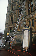 The day after its catastrophic blaze, firefighters continue to assess fire damage from their ladders, to the Queen's official residence at Windsor Castle, on 20th November 1992, in London, England. The most northerly corner of this old building that caught fire in a private chapel on the first floor of the north-east wing. Spreading quickly, damaging St George's Hall, which is often used for banquets. In all, one hundred rooms were damaged in the fire and intense public debate was sparked about whether the taxpayer should foot the repair bill, as the castle is owned by the British Government and not the Royal Family. But the Queen agreed to meet 70% of the costs, and opened Buckingham Palace to the public to generate extra funds. The £40m restoration took five years. Windsor is the largest inhabited castle in the world and partly dates to the time of the Norman King William the Conquerer.