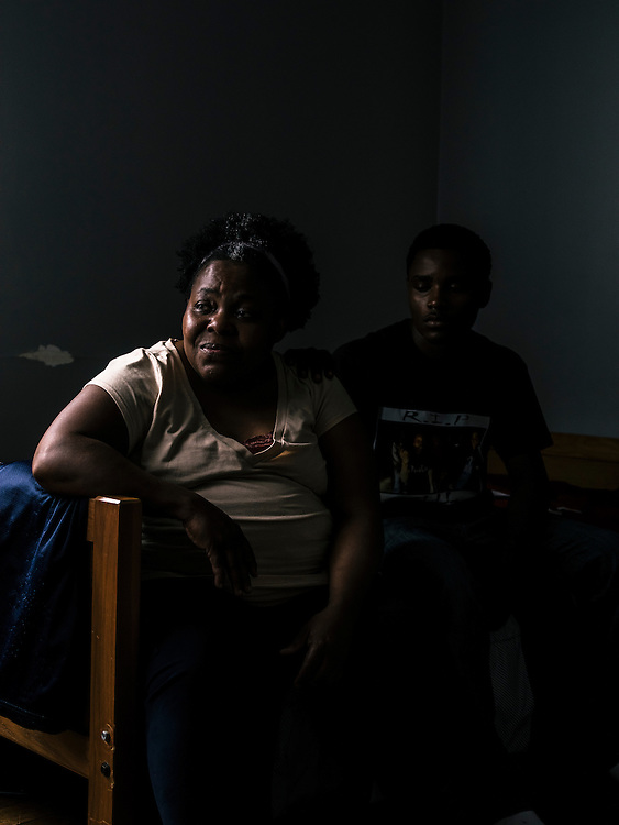 Patricia Lowe, mother of Edward, and Edward's brother, Uriah Span, sit on Edward's bed in his room. Edward is incarcerated in Detroit.