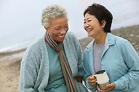 Two female friends talking on beach
