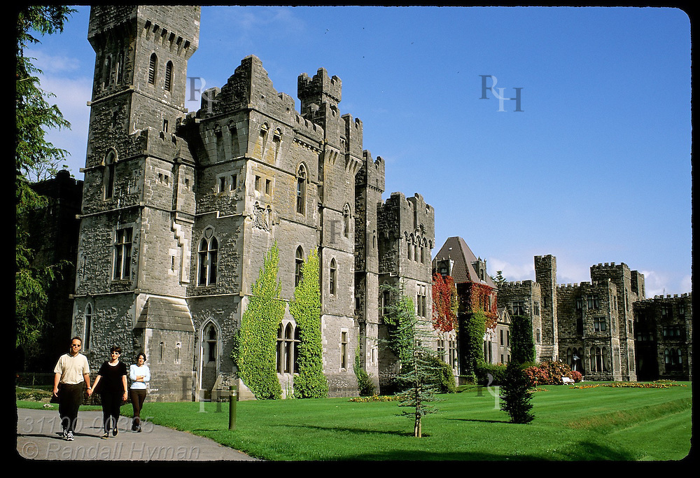Couple walks path outside Ashford Castle, an 83-room hotel counted among Ireland's finest; Cong, Ireland.