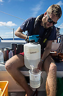 North Atlantic Ocean, October 2014.<br /> Marine biologist Adam Porter examines a sample recovered from a trawl, days away from land, on board the Sea Dragon. &copy; Chiara Marina Grioni