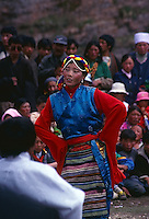 Tibetan woman performing traditional dance at a celebration in the grasslands near Xiahe, China.