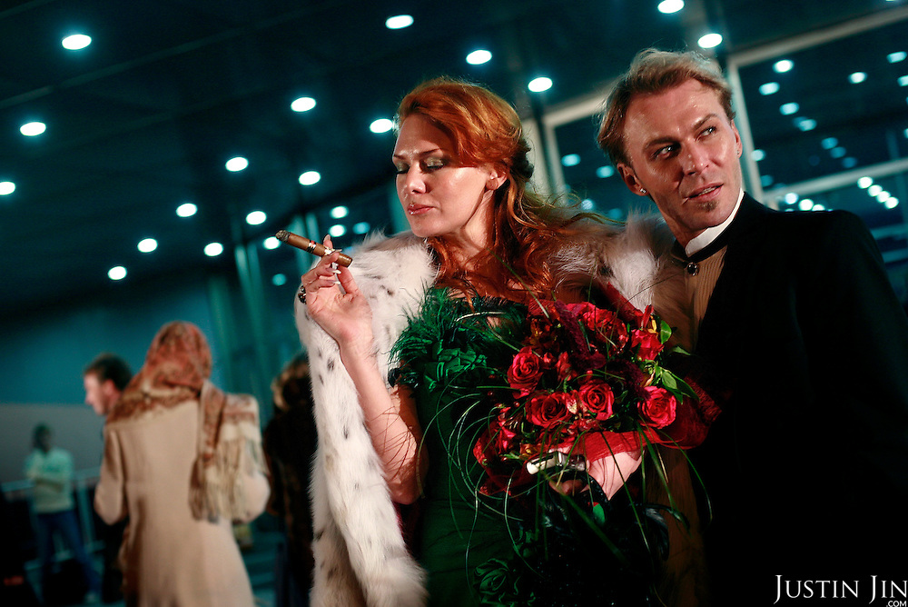 Russian fashion designer Julia Helen, accompanied by an unidentified man, smokes a cigar at the Millionaire Fair in Moscow. .Millionaires, billionaires and those who bought 1,000-rouble tickets were among the thousands who visited the fair held in the Crocus city expo centre. .The four-day event, held for the second year in a row, ended on October 30. The products on sale include a diamond-studded mobile phone worth a million dollars, an island, latest sports cars and other items that might appeal to the growing millionaire market..Twenty years ago, there were no official millionaires in the whole of Russia. Now Moscow has 25 billionaires and the country has 88,000 millionaires, according to Forbes Magazine. ..
