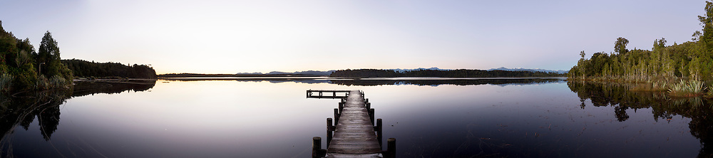 The jetty extends out into the very calm waters of Lake Mahinapua which is surrounded by native forest.