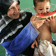 3rd August 2006&amp;#xD;&amp;#xA;Tyre, Lebanon&amp;#xD;&amp;#xA;Refugee Camp&amp;#xD;&amp;#xA;A mother and son in the Rashidiyeh Camp on the outskirts of Tyre which has become home not only to Palestinian refugees but also the Lebanese people who have fled the towns and villages due to Israeli air strikes The two groups now live side by side and are struggling together through the food and fuel shortages caused by this conflict.<br />