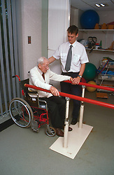 Elderly man with disability; who is wheelchair user; using parallel bars during physiotherapy session,