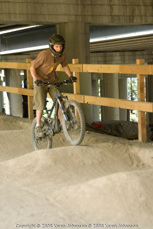 Kim Sturts rides the pump track at the Colonnade bike skills park in Seattle, Wash.