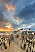 Sand fence at sunrise in front of Kitty Hawk Fishing Pier  on the Outer Banks.